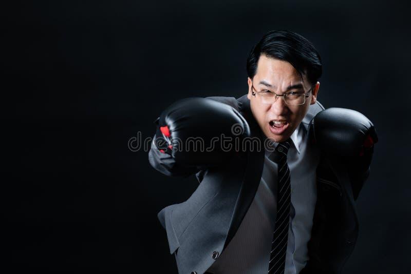 Homem de negócios asiático em luvas de encaixotamento do desgaste do terno imagens de stock royalty free