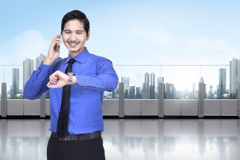 Homem de negócios asiático feliz com telefone que verifica o relógio foto de stock royalty free
