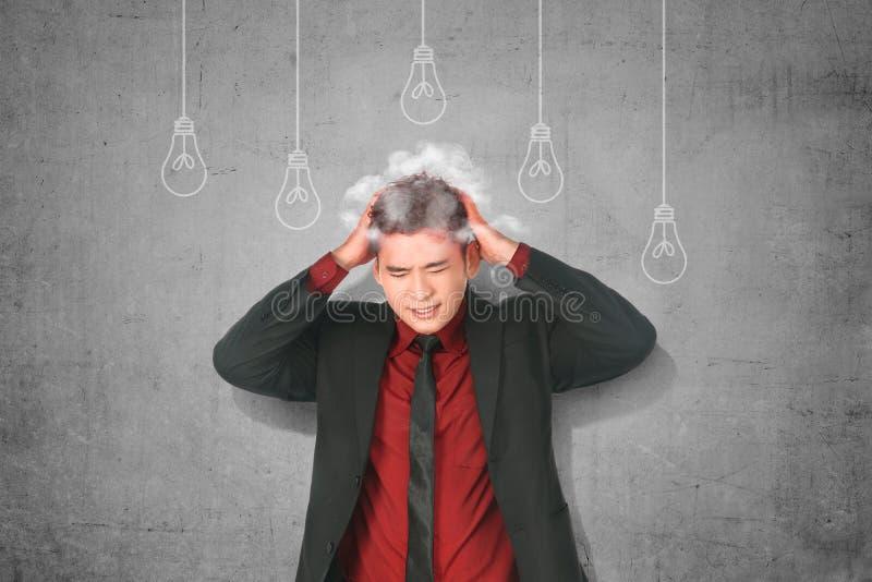 Homem de negócios asiático forçado que pensa para a ideia criativa nova com suspensão da ampola imagens de stock royalty free