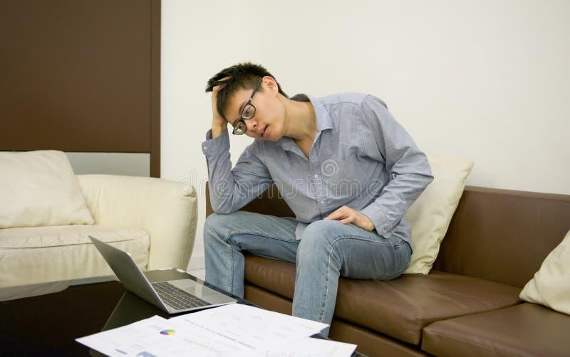 Homem de negócios asiático forçado que usa um portátil na sala de visitas em nigh fotos de stock