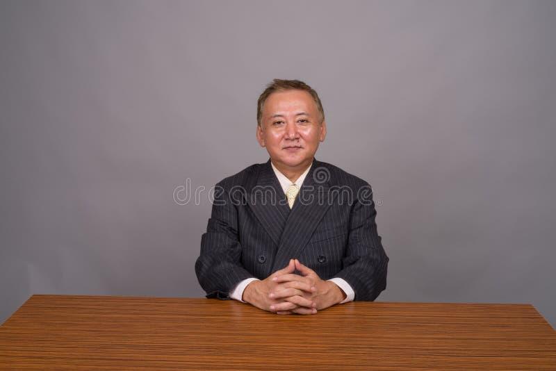 Homem de negócios asiático maduro que senta-se com a tabela de madeira contra o cinza fotografia de stock royalty free
