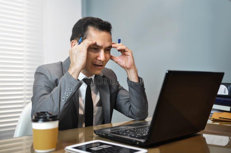Homem de negócios asiático no terno cinzento que pensa e que olha a seu lapto imagens de stock royalty free