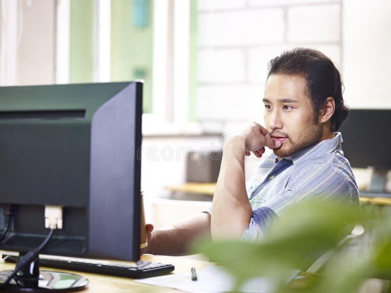 Homem de negócios asiático no vestuário desportivo que trabalha no escritório imagens de stock