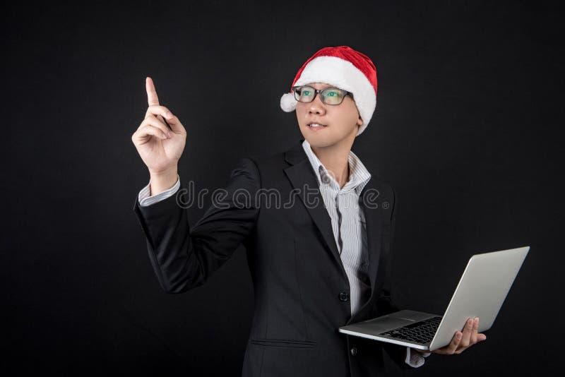 Homem de negócios asiático novo com chapéu de Santa usando o portátil fotos de stock royalty free