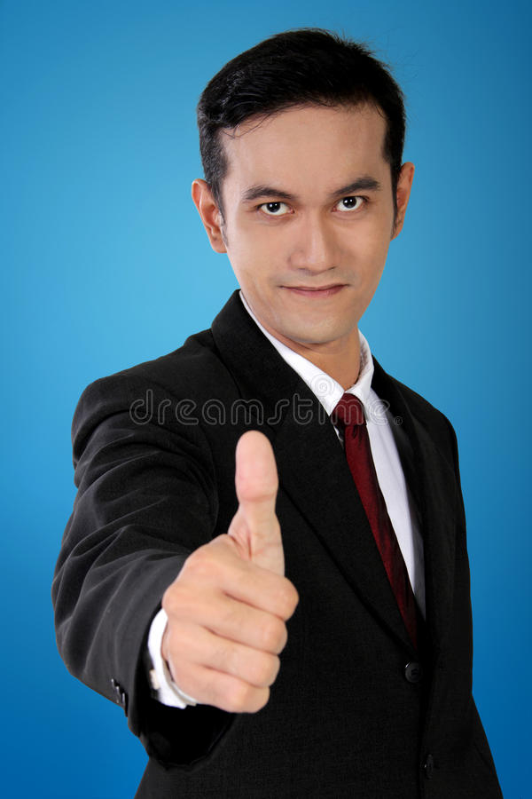 Homem de negócios asiático novo com o polegar acima do gesto, no fundo azul fotos de stock royalty free