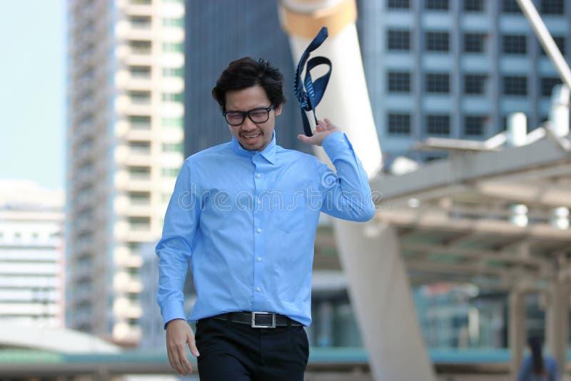 Homem de negócios asiático novo forçado frustrante que anda e que joga sua gravata no fundo urbano da cidade da construção fotografia de stock