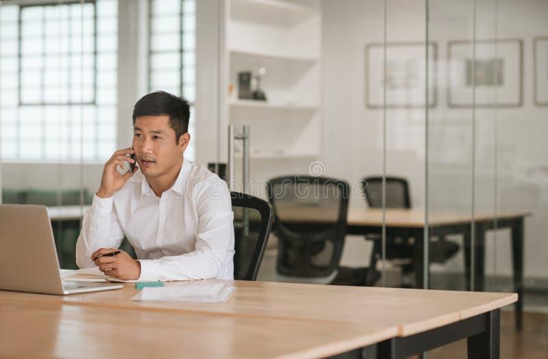 Homem de negócios asiático novo que fala em seu telefone celular em um escritório foto de stock royalty free