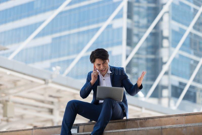 Homem de negócios asiático novo que fala no telefone celular com um f sério foto de stock royalty free