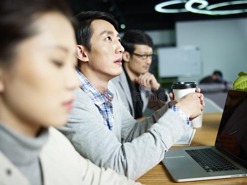 Homem de negócios asiático novo que pensa durante a reunião imagem de stock royalty free