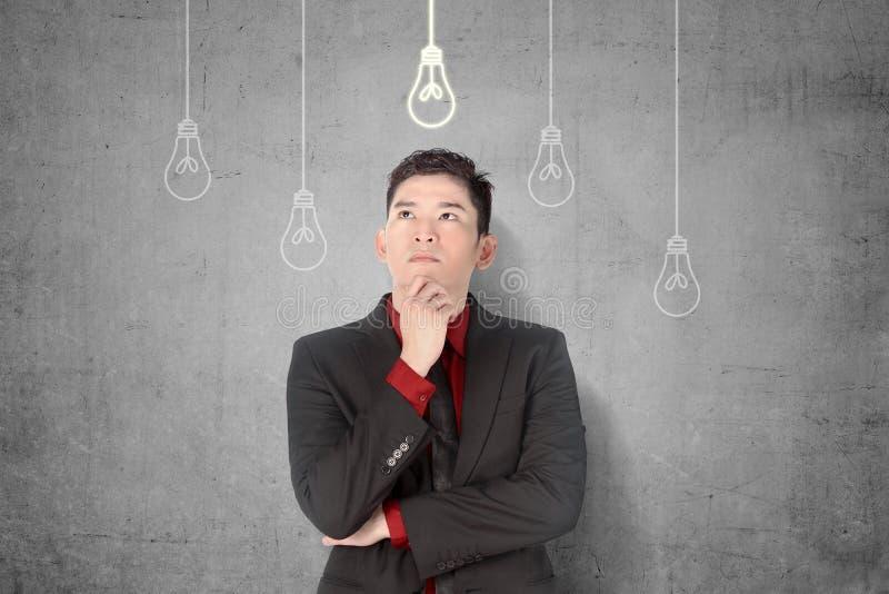 Homem de negócios asiático novo que pensa para a ideia inovativa nova com suspensão brilhante das ampolas imagens de stock