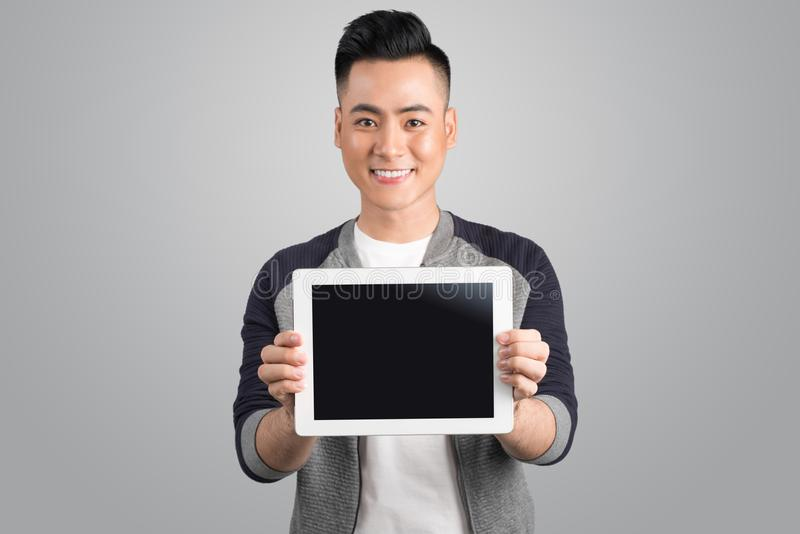 Homem de negócios asiático novo seguro que mostra a tela digital da tabuleta fotografia de stock royalty free