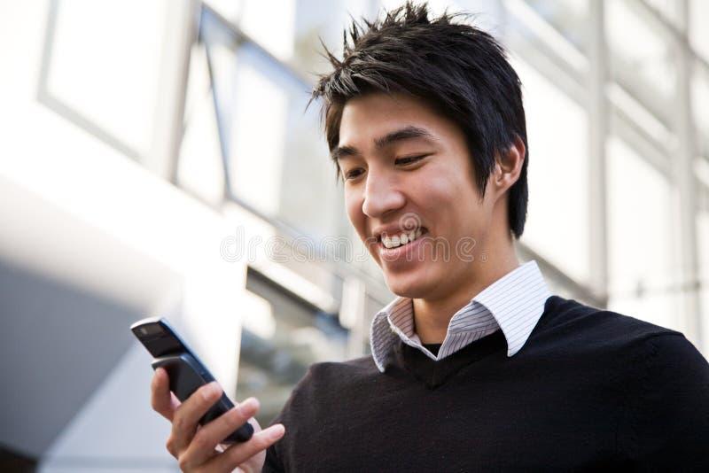 Homem de negócios asiático ocasional que texting fotografia de stock royalty free