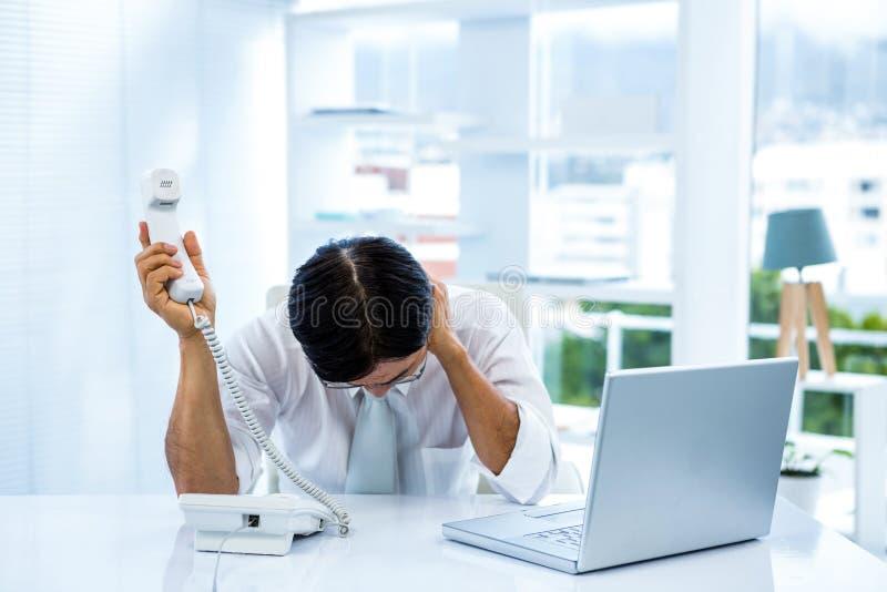 Homem de negócios asiático oprimido que responde ao telefone fotografia de stock royalty free