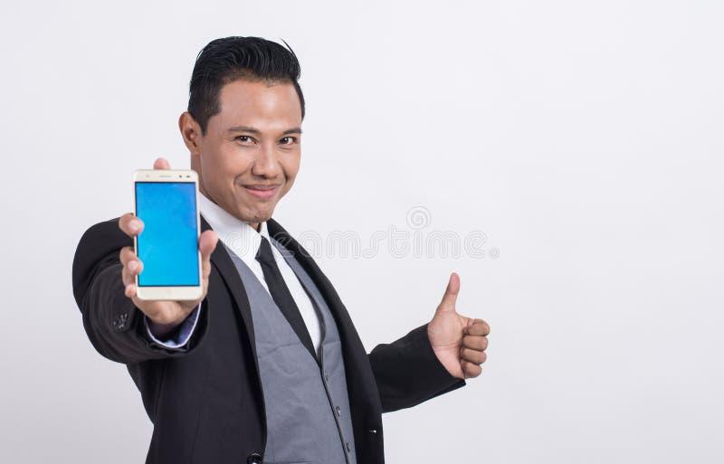 Homem de negócios asiático profissional que mostra um telefone celular e que faz os polegares acima imagem de stock