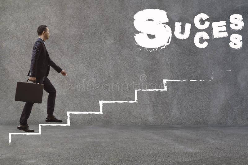 Homem de negócios asiático que anda acima das escadas para encontrar o sucesso Concepti fotografia de stock