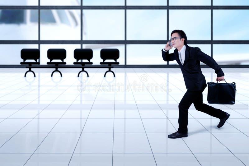 Homem de negócios asiático que corre no aeroporto imagem de stock royalty free