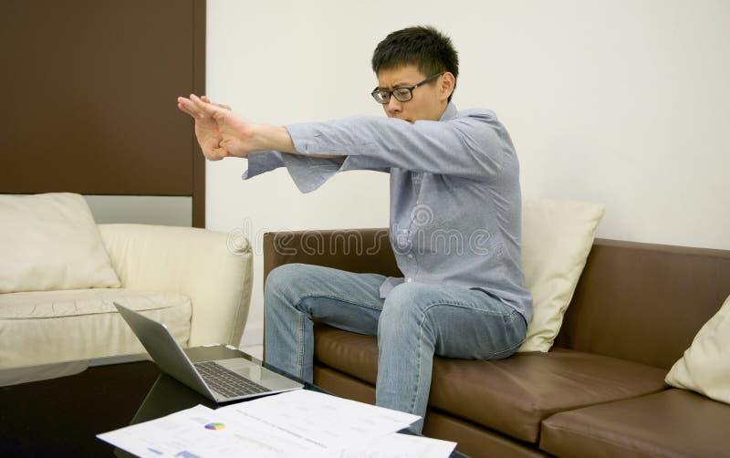 Homem de negócios asiático que estica na frente do portátil com originais fotografia de stock royalty free