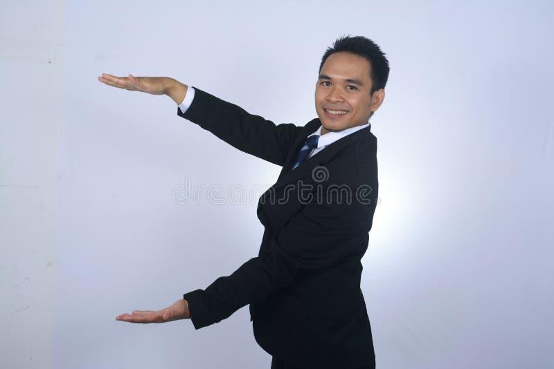 Homem de negócios asiático que guarda a mão com a palma aberta que mostra a algo o gesto, conceito do produto da propaganda, co v fotos de stock royalty free