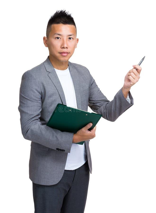 Homem de negócios asiático que guardam com prancheta e pena que aponta acima do som fotografia de stock