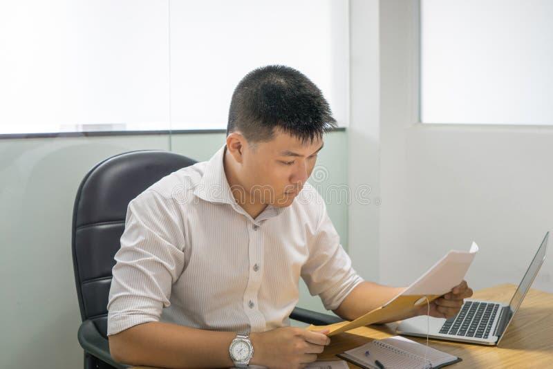 Homem de negócios asiático que lê o documento financeiro no escritório imagens de stock