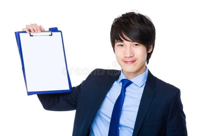 Homem de negócios asiático que mostra a página vazia da prancheta fotografia de stock