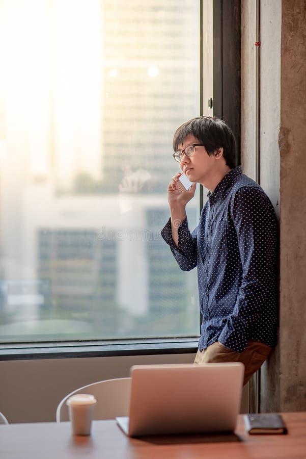 Homem de negócios asiático que usa o smartphone para a conversa do negócio fotos de stock