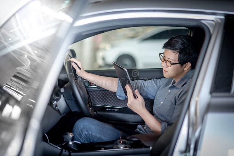 Homem de negócios asiático que usa a tabuleta que senta-se no carro foto de stock