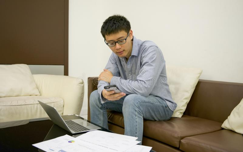 Homem de negócios asiático que usa um portátil na sala de visitas na noite imagem de stock