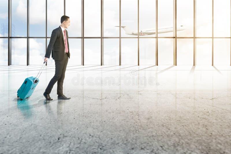 Homem de negócios asiático de sorriso com mala de viagem azul que anda no salão do aeroporto foto de stock