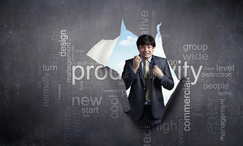 Homem de negócios assustado novo com palavras-chaves de papel rasgadas do furo e do negócio Meios mistos foto de stock