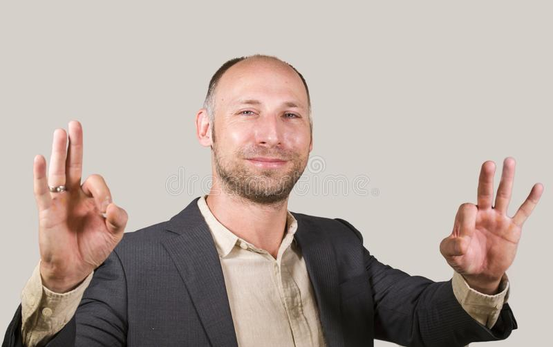 Homem de negócios atrativo e bem sucedido novo que sorri fundo branco feliz e seguro que dá o empresário aprovado do sinal da mão fotografia de stock royalty free