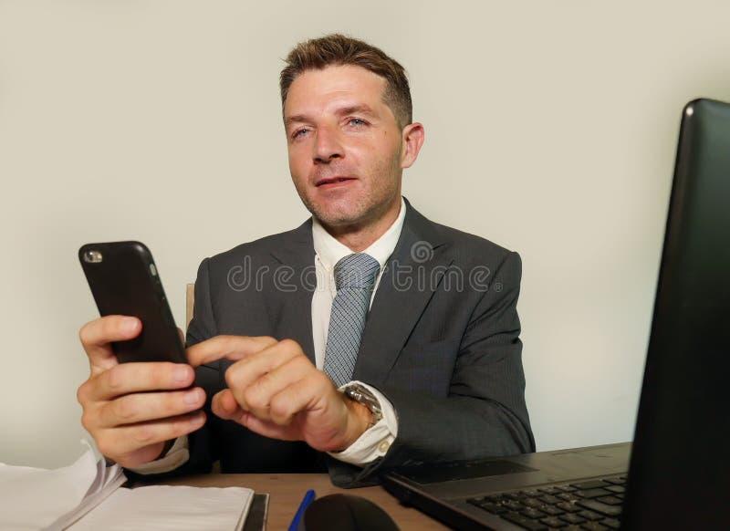 Homem de negócios atrativo e feliz novo no funcionamento do terno e da gravata na mesa do laptop do escritório usando o telefone  foto de stock