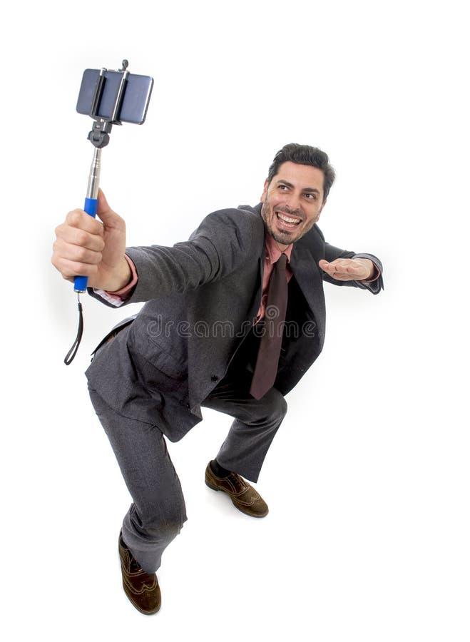 Homem de negócios atrativo novo no terno e laço que toma a foto do selfie com o levantamento da câmera e da vara do telefone celu imagem de stock royalty free