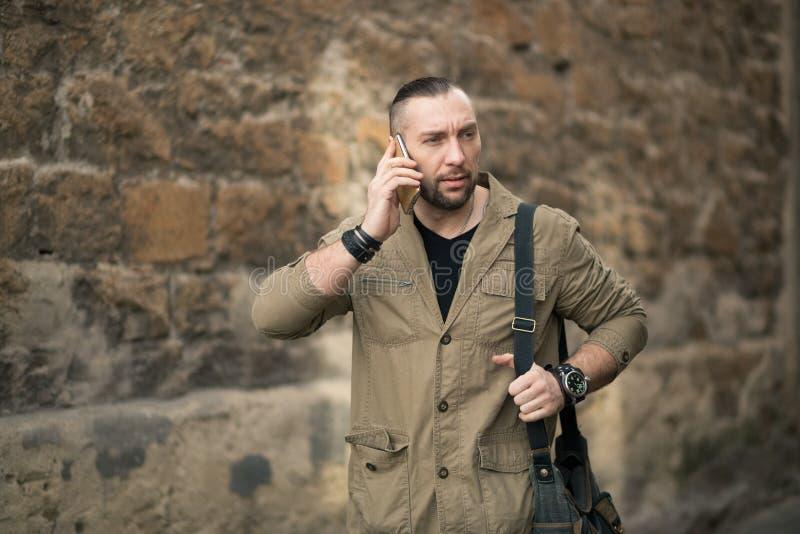 Homem de negócios atrativo que fala no smartphone imagem de stock royalty free