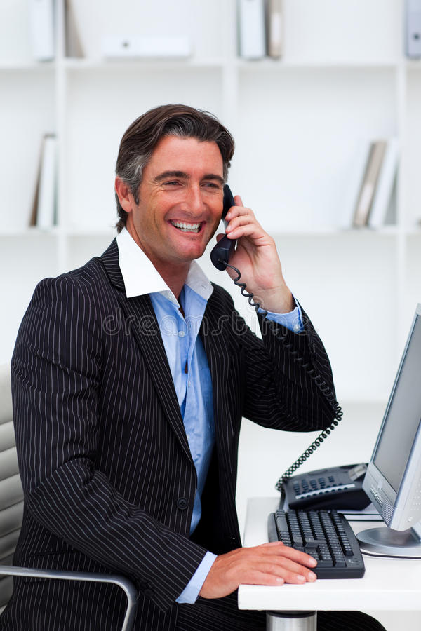 Homem de negócios atrativo que faz um atendimento de telefone foto de stock