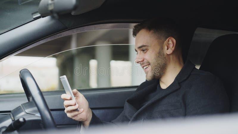 Homem de negócios atrativo que senta-se dentro do carro que ri ao usar o smartphone após a viagem fotografia de stock