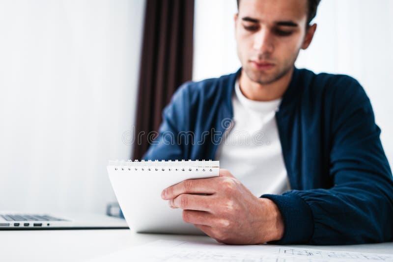 Homem de negócios atrativo que trabalha no escritório no portátil e no bloco de notas ao sentar-se na tabela fotografia de stock royalty free