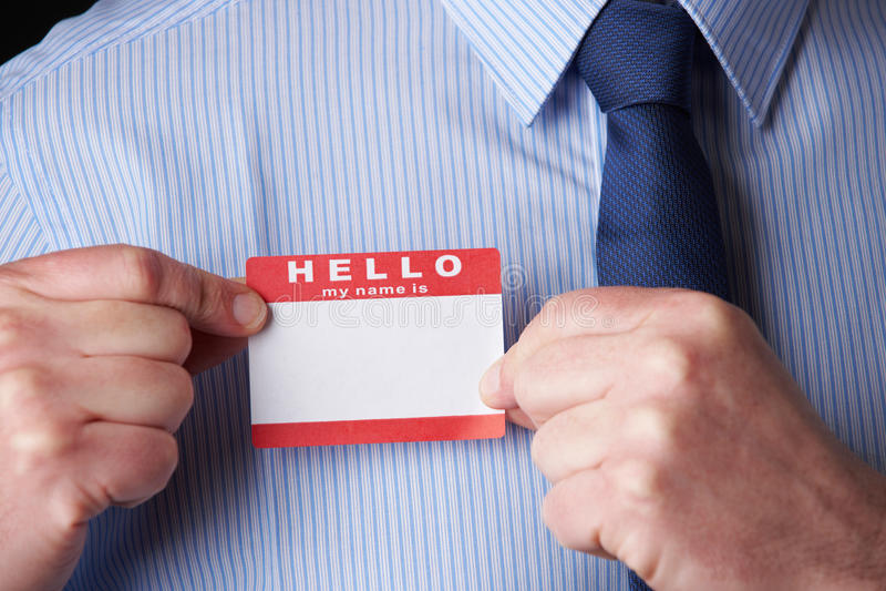 Homem de negócios Attaching Name Tag na conferência foto de stock