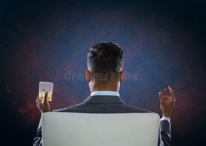 Homem de negócios Back Sitting na cadeira com vidro da bebida e fundo escuro imagens de stock royalty free