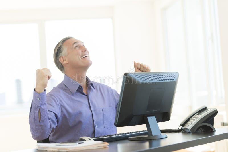 Homem de negócios bem sucedido With Clenched Fist que olha acima no escritório fotos de stock royalty free