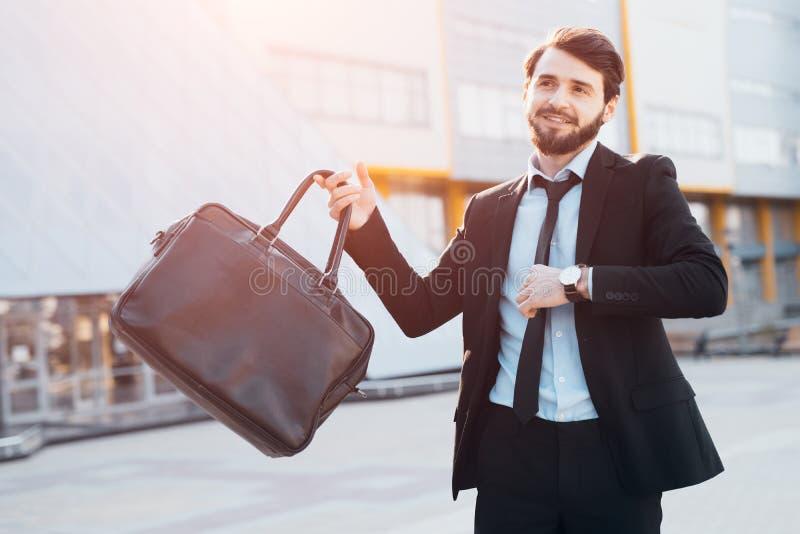 Homem de negócios bem sucedido com o saco preto no fundo da construção do escritório fotografia de stock