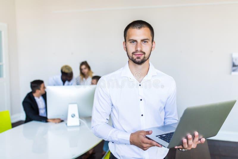 Homem de negócios bem sucedido com portátil que sorri na câmera quando seus colegas que estão atrás dele no escritório fotos de stock royalty free