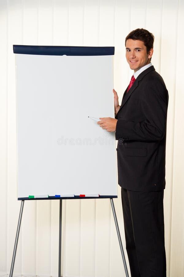 Homem de negócios bem sucedido com um flipchart para imagem de stock