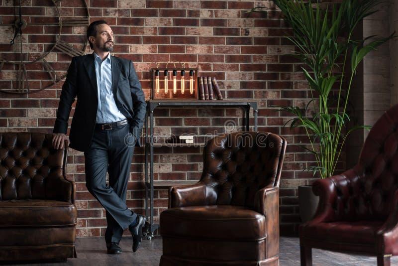 Homem de negócios bem sucedido considerável que está em sua sala de estudo foto de stock royalty free