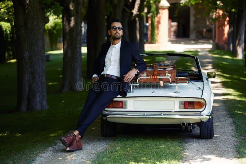 Homem de negócios bem sucedido e rico que aprecia um dia durante a viagem no carro luxuoso do cabriolet na estrada do campo imagem de stock royalty free