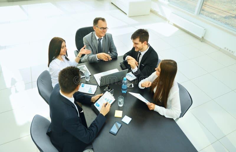 Homem de negócios bem sucedido e sua reunião da equipe do negócio fotos de stock