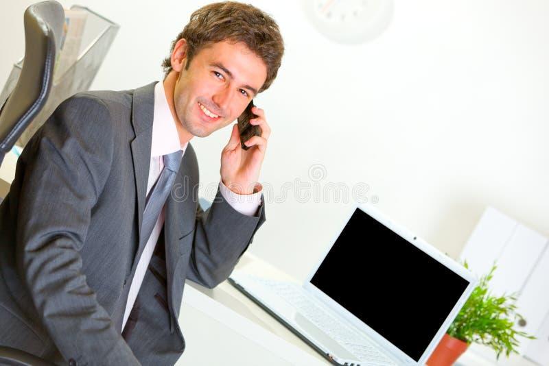 Homem de negócios bem sucedido no escritório que faz o atendimento de telefone foto de stock