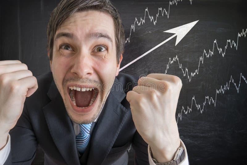 Homem de negócios bem sucedido novo e cartas crescentes no quadro-negro no fundo fotografia de stock royalty free