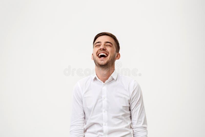 Homem de negócios bem sucedido novo que sorri, rindo sobre o fundo branco imagem de stock royalty free