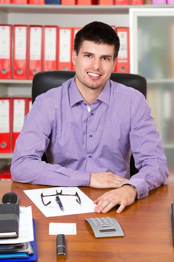 Homem de negócios bem sucedido novo que trabalha em sua mesa fotos de stock royalty free